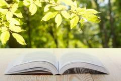Offenes Buch auf Holztisch auf natürlichem unscharfem Hintergrund Herzbuchseite Zurück zu Schule Kopieren Sie Platz Stockbild