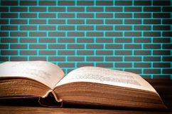 Offenes Buch auf Oberfläche auf Backsteinmauerhintergrund lizenzfreie stockfotos