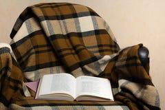 Offenes Buch auf Stuhl mit einer gestrickten Decke, englisch stockbilder