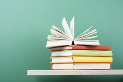 Offenes Buch, Bücher des gebundenen Buches auf hölzernem Regal Scheren und Bleistifte auf dem Hintergrund des Kraftpapiers Zurück Lizenzfreies Stockfoto