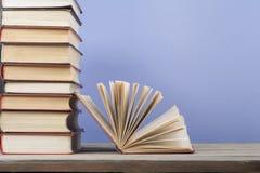 Offenes Buch, Bücher des gebundenen Buches auf Holztisch Scheren und Bleistifte auf dem Hintergrund des Kraftpapiers Zurück zu Sc Lizenzfreie Stockfotografie