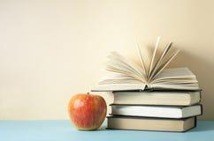 Offenes Buch, Bücher des gebundenen Buches und Apfel auf Holztisch Scheren und Bleistifte auf dem Hintergrund des Kraftpapiers Zu Lizenzfreies Stockbild