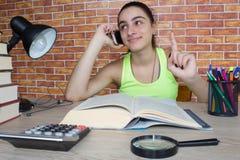 Offenes Buch, bunte Bücher des gebundenen Buches auf Holztisch Junges Mädchen, das zu Hause am Schreibtisch, Hausarbeit tuend sit Lizenzfreie Stockfotos