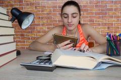 Offenes Buch, bunte Bücher des gebundenen Buches auf Holztisch Junges Mädchen, das zu Hause am Schreibtisch, Hausarbeit tuend sit Stockfotos