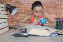 Offenes Buch, bunte Bücher des gebundenen Buches auf Holztisch Junges Mädchen, das zu Hause am Schreibtisch, Hausarbeit tuend sit Lizenzfreie Stockbilder