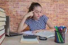 Offenes Buch, bunte Bücher des gebundenen Buches auf Holztisch Junges Mädchen, das zu Hause am Schreibtisch, Hausarbeit tuend sit Stockbilder