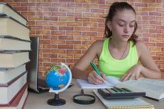 Offenes Buch, bunte Bücher des gebundenen Buches auf Holztisch Junges Mädchen, das zu Hause am Schreibtisch, Hausarbeit tuend sit Lizenzfreies Stockbild