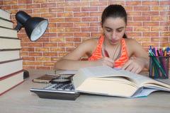 Offenes Buch, bunte Bücher des gebundenen Buches auf Holztisch Junges Mädchen, das zu Hause am Schreibtisch, Hausarbeit tuend sit Lizenzfreies Stockfoto