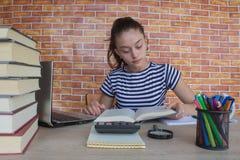 Offenes Buch, bunte Bücher des gebundenen Buches auf Holztisch Junges Mädchen, das zu Hause am Schreibtisch, Hausarbeit tuend sit Stockbild