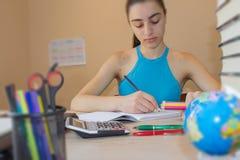 Offenes Buch, bunte Bücher des gebundenen Buches auf Holztisch Mädchen, das zu Hause am Schreibtisch, Hausarbeit tuend sitzt getr Stockfotos