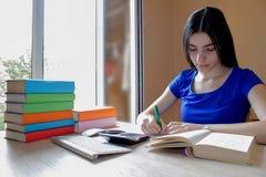 Offenes Buch, bunte Bücher des gebundenen Buches auf Holztisch Mädchen, das zu Hause am Schreibtisch, Hausarbeit tuend sitzt getr Stockfoto