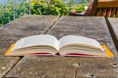 Offenes Buch, das auf einer Tabelle im Freien liegt Stockfotografie