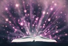 Offenes Buch, das funkelndes Licht ausstrahlt Stockfoto
