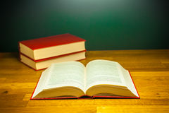 Offenes Buch des Wissens auf hölzerner Schreibtischtabelle in der Bibliothek Stockbild