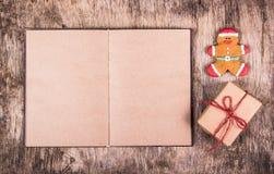 Offenes Buch, Lebkuchenmann und Geschenkbox Jemand in gestreiften Strümpfen tiptoe zum Weihnachtsbaum Festliche Hintergründe stockbilder