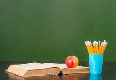 Offenes Buch mit Apfel und Bleistifte nähern sich leerer grüner Tafel Probe für Text Stockfotografie