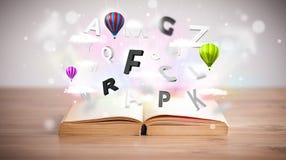 Offenes Buch mit dem Fliegen von Buchstaben 3d auf konkretem Hintergrund Stockfotos