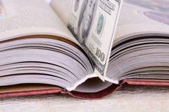 Offenes Buch mit einem Bookmark $ 100 Stockbilder