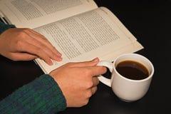 Offenes Buch mit einem Tasse Kaffee am schwarzen Tisch lizenzfreie stockfotos