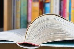 Offenes Buch mit einer Bibliothek im Hintergrund Stockbild