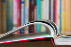 Offenes Buch mit einer Bibliothek im Hintergrund Stockbilder
