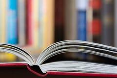 Offenes Buch mit einer Bibliothek im Hintergrund Lizenzfreie Stockfotos