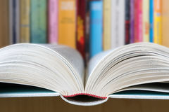 Offenes Buch mit einer Bibliothek im Hintergrund Lizenzfreie Stockbilder