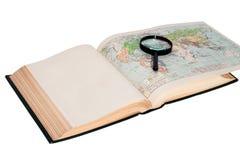 Offenes Buch mit einer Karte und einer Lupe Stockfoto