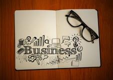 Offenes Buch mit Gläsern und schwarzem Geschäft kritzelt auf Tabelle Lizenzfreie Stockfotos