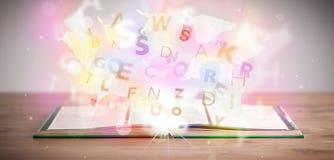Offenes Buch mit glühenden Buchstaben auf konkretem Hintergrund stockfotos