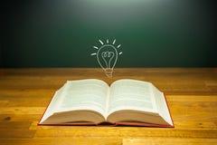 Offenes Buch mit Glühlampe für Ideenkonzept Stockbild