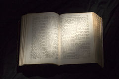 Offenes Buch mit hellem Scheinwerfer auf Text Lesung geöffneten Buches e Lizenzfreie Stockfotografie