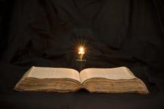 Offenes Buch mit hellem Scheinwerfer auf Text Lesung geöffneten Buches e Stockfotos