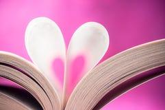 Offenes Buch mit Herzform auf rosa Hintergrund - Tal Stockfotografie