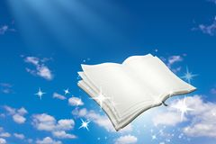 Offenes Buch mit magischem Scheinfliegen auf Hintergrund des blauen Himmels Lese- und Schreibenskonzept lizenzfreies stockbild