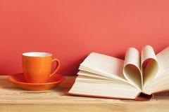 Offenes Buch mit Seiten in Form von dem Herzen auf rotem Hintergrund Freiexemplarraum getrennte alte Bücher Stockbilder