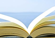 Offenes Buch mit unscharfen Türkisblautönen von Meer und von Himmel im Hintergrund lizenzfreie stockfotos