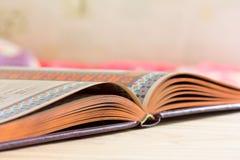 Offenes Buch mit vergoldetem Rand auf dem Tisch Lizenzfreies Stockfoto