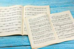 Offenes Buch, Noten Musikalische Anmerkungen über einen weißen Holztisch Hintergrund Stockfotos