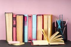 Offenes Buch, Stapel des bunten gebundenen Buches bucht zurück zu Schule Scheren und Bleistifte auf dem Hintergrund des Kraftpapi Stockfotos