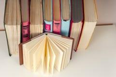 Offenes Buch, Stapel des bunten gebundenen Buches bucht zurück zu Schule Scheren und Bleistifte auf dem Hintergrund des Kraftpapi Lizenzfreies Stockbild