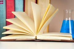 Offenes Buch, Stapel des bunten gebundenen Buches bucht zurück zu Schule Scheren und Bleistifte auf dem Hintergrund des Kraftpapi Lizenzfreies Stockfoto
