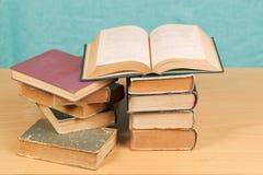 Offenes Buch, Stapel des gebundenen Buches reserviert auf Holztisch Lizenzfreies Stockbild