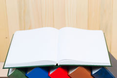 Offenes Buch, Stapel des gebundenen Buches reserviert auf Holztisch Stockbilder