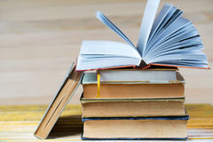 Offenes Buch, Stapel des gebundenen Buches reserviert auf Holztisch Stockfoto
