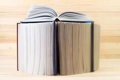 Offenes Buch, Stapel des gebundenen Buches reserviert auf Holztisch Zurück zu Schule Kopieren Sie Platz Lizenzfreie Stockbilder