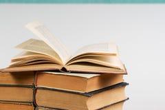 Offenes Buch, Stapel des gebundenen Buches reserviert auf Tabelle Stockfotografie