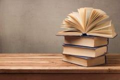 Offenes Buch und Stapel alte Bücher auf Holztisch Lizenzfreie Stockfotos