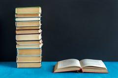 Offenes Buch und Stapel Bücher Lizenzfreies Stockfoto