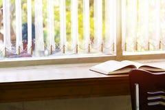 Offenes Buch wird auf dem Tisch am Fenster gesetzt Lizenzfreie Stockfotografie